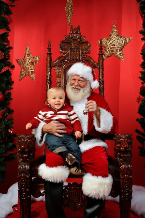 Baby boy sitting on Santa photo