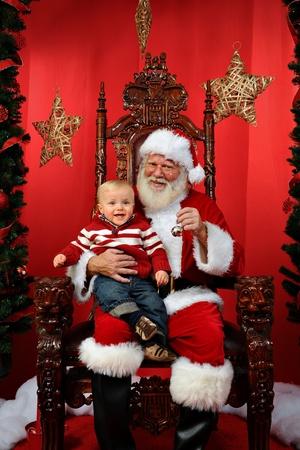 �santaclaus: Beb� sentado en Santa Foto de archivo