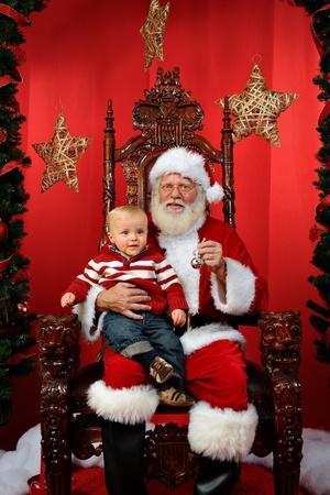 Baby boy sitting on Santa photo