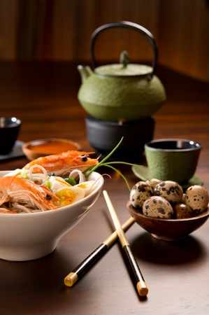 Beautifully prepared prawns and quail eggs served over noodles. Chopsticks, a bowl with sauce, a tea cup, a tea pot and a bowl of quail eggs are also on the table. Imagens
