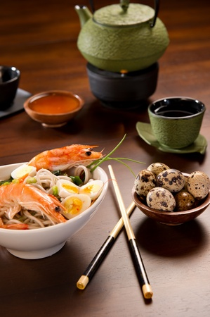 Beautifully prepared prawns and quail eggs served over noodles. Chopsticks, a bowl with sauce, a tea cup, a tea pot and a bowl of quail eggs are also on the table. Stockfoto