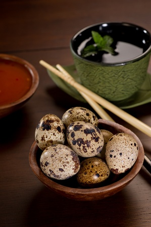 japanese quail: Delicate, beautiful Quail Eggs in a wood bowl.  A green cast iron tea cup is to the side along with chopsticks and a bowl of red dipping sauce.  Shallow depth of field.