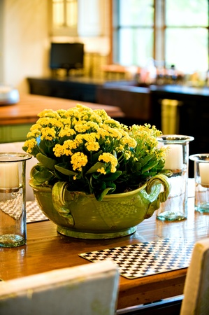 Beautiful yellow flower arrangement on the dining room table. photo