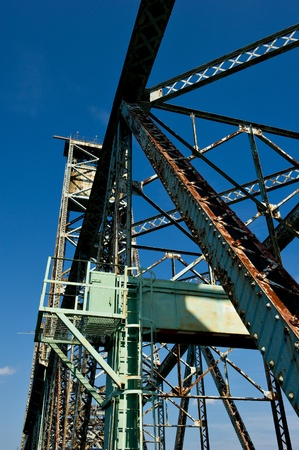 Looking up at a rusty old brown and green bridge against the blue sky in Portsmouth, New Hampshire. Stock Photo - 11839416
