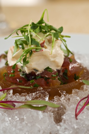 Raw ahi tuna tartare appetizer topped with seafood crab salad over ice and garnished with fresh green sprouts. Served with a side of tempura tortilla chips photo