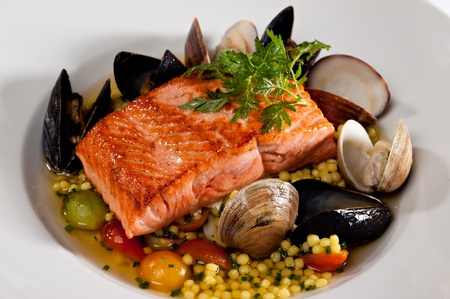pink salmon: Beautifully plated salmon fillet garnished with colorful green parsley.  Served over a couscous and seafood salad featuring mussels, clams, tomatoes and brussels sprouts.