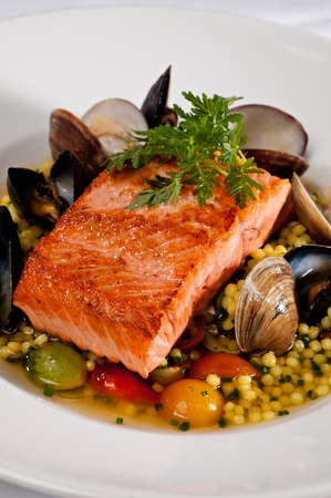 Beautifully plated salmon fillet garnished with colorful green parsley.  Served over a couscous and seafood salad featuring mussels, clams, tomatoes and brussels sprouts.  photo