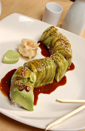 saki: Japanese Avocado Roll (or Caterpillar Roll) with Eel Sauce on a white plate.  There is a rose made of ginger and a leaf made of wasabi on the side.  Chopsticks and a saki set in the background.