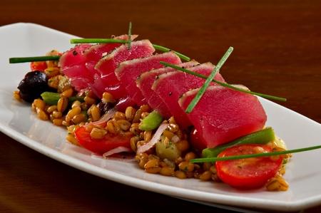 Frais, belle rose brute thon ahi sashimi servi sur une salade d'orge. Le tout servi sur une assiette blanche.