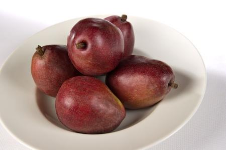 anjou: Bol blanco que contiene 5 peras Anjou rojas.