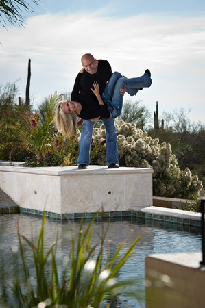 he: Full length of a happy playful couple posing next to a pool. He appears to be about to drop her in the pool. A green winter desert landscape is in the background.