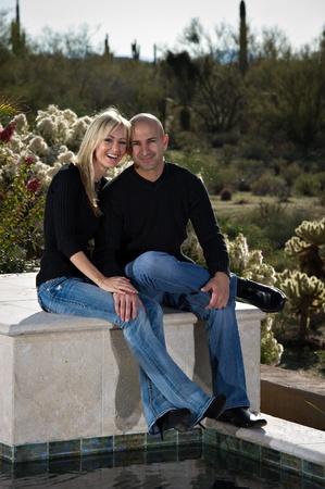 De cuerpo entero de una pareja feliz juguetona posando junto a una piscina. Un paisaje de invierno desierto verde está en el fondo.