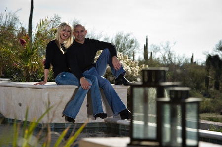 high desert: Full length of a happy playful couple posing next to a pool. A green winter desert landscape is in the background.