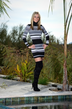 Full length of a beautiful young woman posing next to a pool. She is wearing a short striped sweater dress and black stiletto boots.