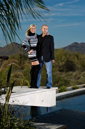 Full length of a happy couple posing next to a pool. A green winter desert landscape is in the background. photo