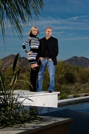 Full length of a happy couple posing next to a pool. A green winter desert landscape is in the background.