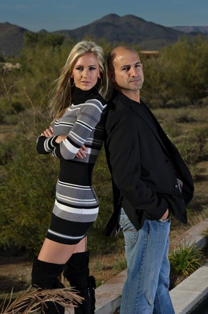 Full length of a happy couple posing back to back. A green winter desert landscape is in the background. photo