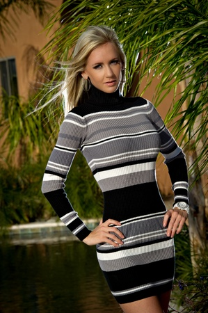 Beautiful young woman posing next to a pool. She is wearing a short stripped sweater dress with her hands on her hips; and her hair is blowing in the breeze. Stock Photo