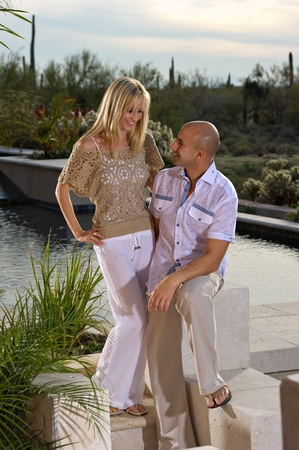 Beautiful happy couple posing next to a pool.   A green winter desert landscape is in the background. photo