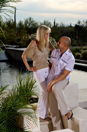 Full length of a beautiful happy couple posing next to a pool.   A green winter desert landscape is in the background. photo