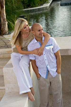 Beautiful happy couple posing next to a pool.   She is sitting and he is standing. photo