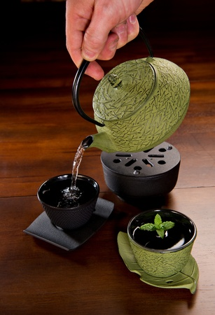 Tea being poured in a traditional Japanese cast iron tea pot and cups. photo