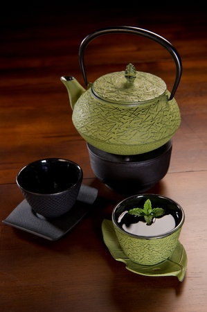 Tea served in a traditional Japanese cast iron tea pot and cups. Stock Photo