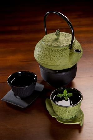 cast iron: Tea served in a traditional Japanese cast iron tea pot and cups.