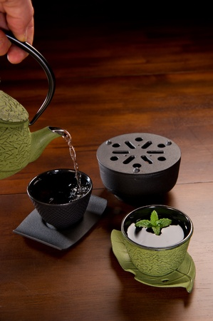 Tea being poured in a traditional Japanese cast iron tea pot and cups. Stock Photo