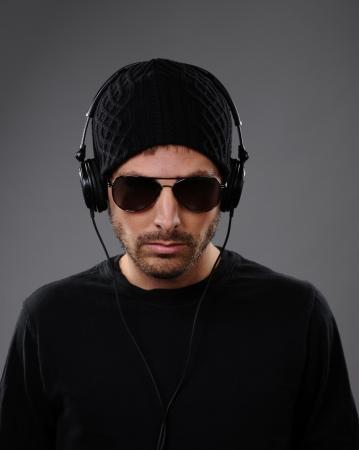 DJ listening to headphones on a dark background. Фото со стока