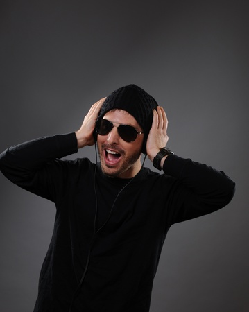 DJ listening to headphones on a dark background.  He appears to be speaking or shouting as to get the party started. photo