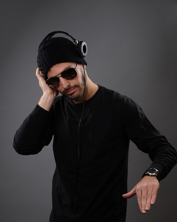 DJ listening to headphones on a dark background.  His hand is out as he is about to spin a record.