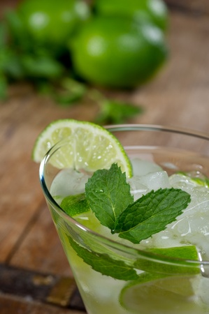 Fresh mojito in a lowball glass on a rustic table garnished with limes and mint leaves. 免版税图像