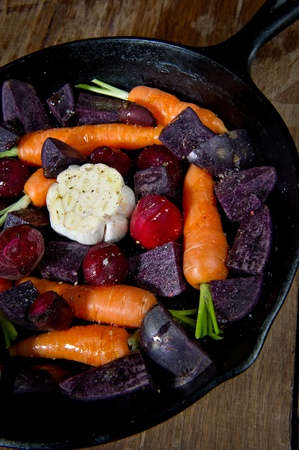 cast iron: Raw root vegetables in a cast iron skillet ready for the oven and shot from above. Vegetables include carrots, red beets, garlic and purple potatoes.