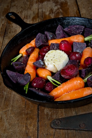Raw root vegetables in a cast iron skillet ready for the oven and shot from above. Vegetables include carrots, red beets, garlic and purple potatoes. photo