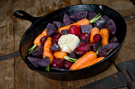 cast iron: Raw root vegetables in a cast iron skillet ready for the oven. Vegetables include carrots, red beets, garlic and purple potatoes.