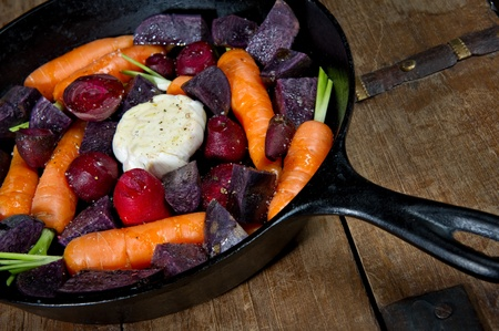 Raw root vegetables in a cast iron skillet ready for the oven. Vegetables include carrots, red beets, garlic and purple potatoes. photo