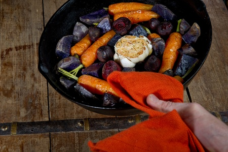 Roasted root vegetables in a cast iron skillet. Vegetables include carrots, red beets, garlic and purple potatoes.  photo