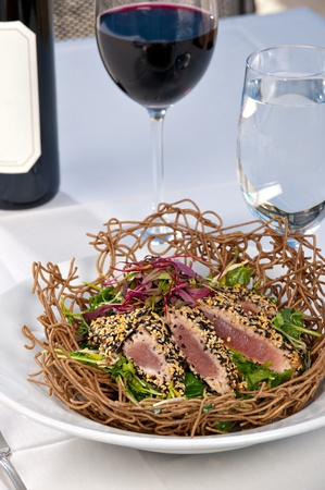 seared: Fresh raw ahi tuna sashimi served over a green salad in an edible bowl made of noodles. All served on a white plate with red wine.