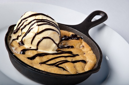 Skillet Baked Chocolate Chip Cookie dessert topped with ice cream and chocolate sauce drizzled. Foto de archivo