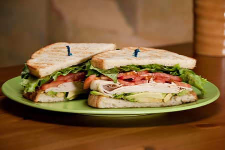 A deli classic turkey sandwich with plenty of turkey, avocado, tomato, and lettuce on white toasted bread.
