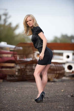 hands on hips: Beautiful blond fashion model with her hands on her hip and her head tilted up, wearing a short black skirt posing at a construction site outdoors. Stock Photo