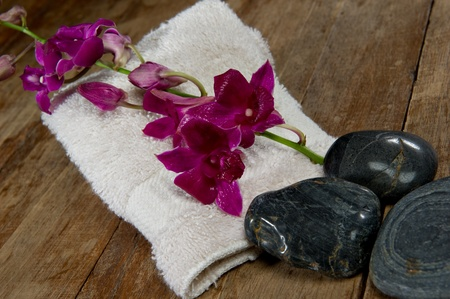 Vibrant pick orchid lays on a spa towel next to black stones.