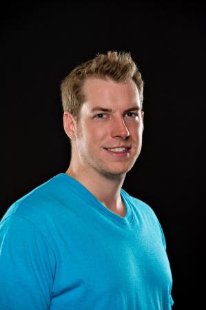 blonde yeux bleus: Portrait d'un jeune modèle masculin portant un t-shirt bleu tiré sur un fond noir Ses bras sont croisés et il a une expression heureuse