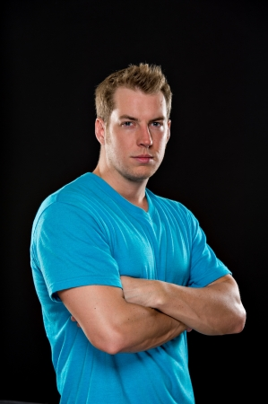 black hair blue eyes: Portrait of a young male model wearing a blue t-shirt shot on a black background   His arms are crossed and he has a serious expression  Stock Photo