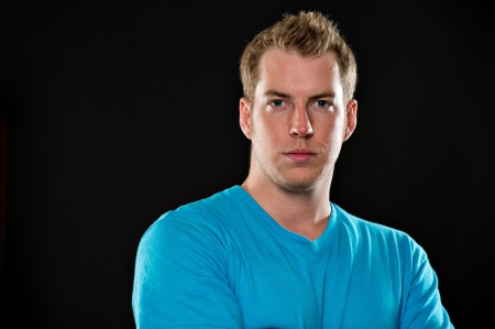 dark eyes: Portrait of a young male model wearing a blue t-shirt shot on a black background.  His arms are crossed and he has a serious expression.