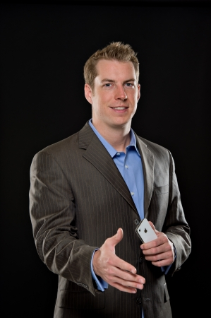 man front view: Portrait of a young male model wearing a suit jacket.  Hes smiling with confidence and expending his hand for a hand shake.