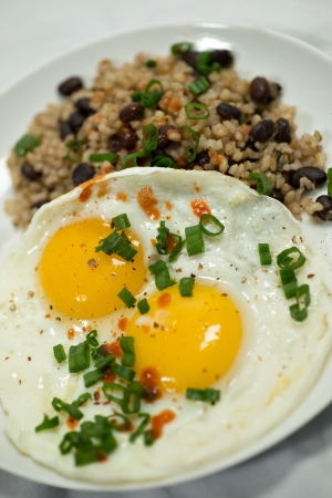 Beautifully plated breakfast featuring 2 eggs served sunny side up, over brown rice and black beans   All topped with fresh scallions and hot sauce  Shot on a white background  photo