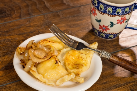 semicircular: A plate of handmade pierogi with a side of caramelized onions   Stock Photo
