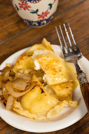 semicircular: A plate of handmade pierogi with a side of caramelized onions   There is a decorative silver and wood fork on the plate, as well as a colorful mug in the background   Everything is shot on a wood table